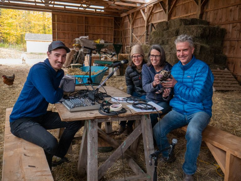 Podcast guests sitting around a table inside a barn