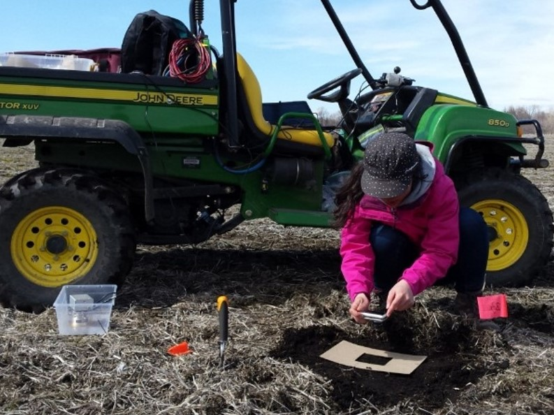 Researcher taking a photo of soil with their cell phone