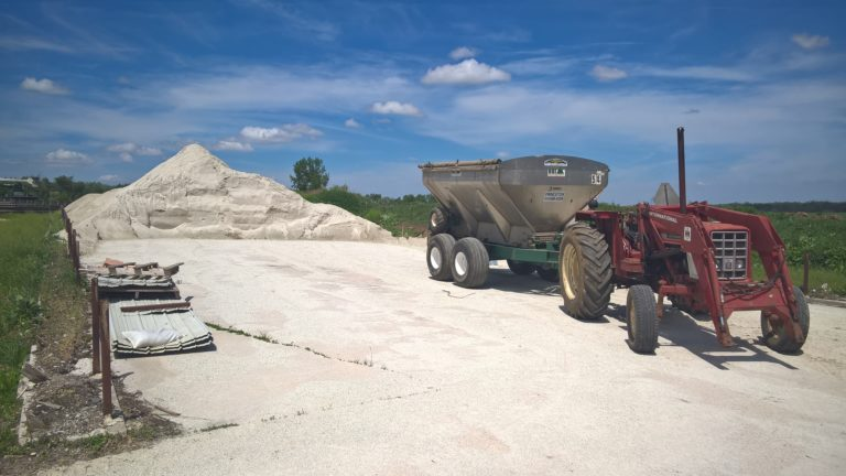 Tractor with fertilizer spreader next to a pile of rock fertilizer